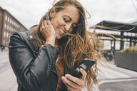 Happy young woman with windswept hair using cell phone in the city - KNSF04005