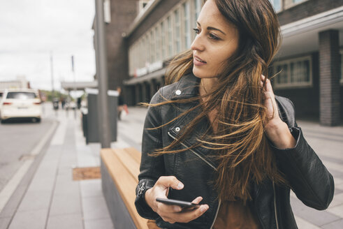Young woman with windswept hair holding cell phone in the city - KNSF04008