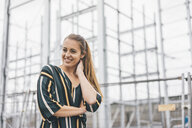 Portrait of smiling young woman at scaffolding - KNSF04011