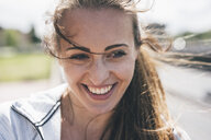 Portrait of smiling sportive young woman outdoors - KNSF04026