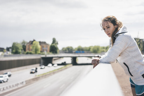 Sportive young woman leaning on railing at motorway - KNSF04032