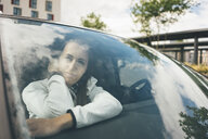 Sportive young woman in car looking out of window - KNSF04038