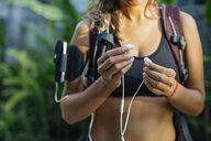 Thailand, Koh Phangan, Sportive woman with earphones, preparing to workout - MOMF00454