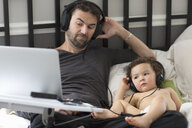 Father and toddler daughter reclining in bed listening to music on headphones - ISF12863