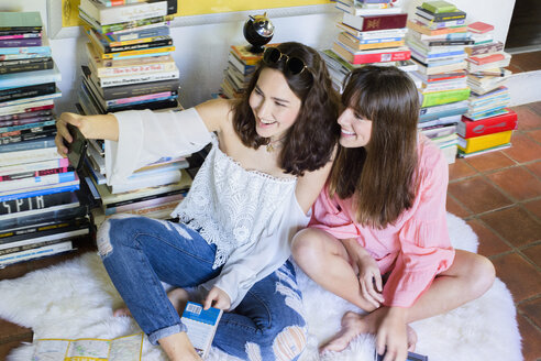 Two young female friends sitting on floor taking smartphone selfie - ISF12869