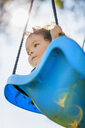 Young girl on playground swing, low angle view - ISF12872