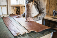 Leather craftsman with strips of leather on workshop bench - ISF12917