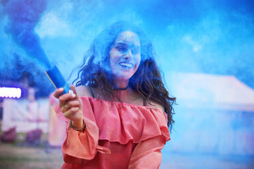 Happy woman holding smoke bomb at music festival - ABIF00637