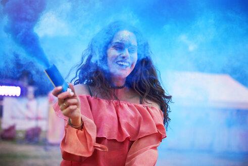 Happy woman holding smoke bomb at music festival - ABIF00637