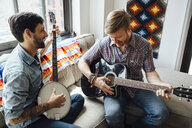Male couple at home, play guitar and banjo, laughing - ISF13037