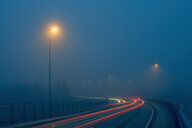 Diminishing perspective of light trails on misty road illuminated by street lights, Haugesund, Rogaland County, Norway - ISF13087