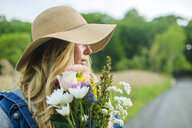 Portrait of young woman with bunch of flowers and wearing straw hat - ISF13186