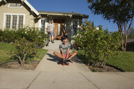 Boy skateboarding down garden path - ISF13258