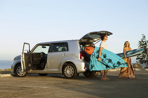 Couple taking surfboards from boot of car - ISF13348