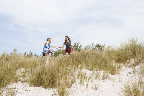 Two young female friends running and holding hands on sand dunes - ISF13372