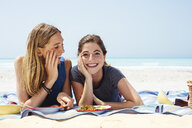 Portrait of two young female friends lying on picnic blanket at beach - ISF13384