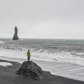 Young male tourist looking out to sea from rock formation,  Reynisfjara, Iceland - ISF13435