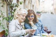 Two mature female friends looking at smartphone at sidewalk cafe, Tuscany, Italy - ISF13447