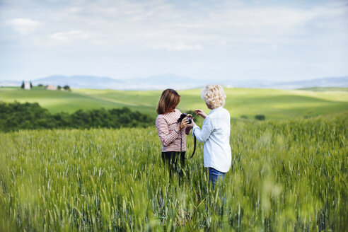 Two mature female friends with digital camera in wheatfield, Tuscany, Italy - ISF13465
