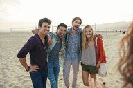Group of friends standing together on beach, laughing - ISF13525