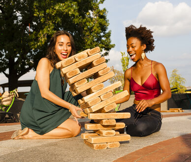 Young women playing with building blocks on floor - ISF13588