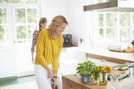 Woman opening wine bottle in kitchen - ISF13636