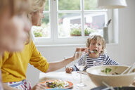 Mother feeding son at dining table - ISF13645