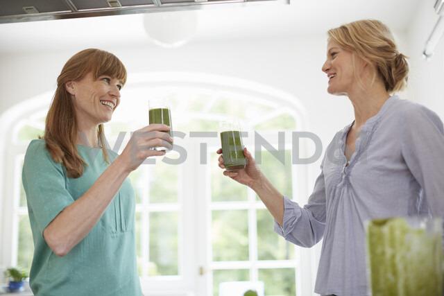 Women drinking green vegan smoothie in kitchen - ISF13651