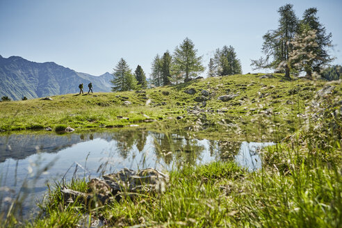 Young hiking couple in distant landscape, Karthaus, Val Senales, South Tyrol, Italy - ISF13696