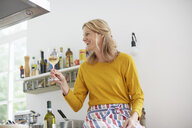 Woman holding up wine glass in kitchen - ISF13813