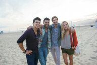Group of friends standing together on beach, laughing - ISF13867