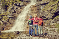 Three children standing by waterfall, rear view - ISF13960