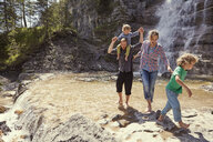 Two generation family having fun by waterfall, Ehrwald, Tyrol, Austria - ISF13972