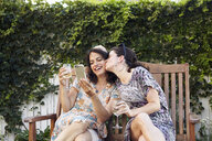 Two women posing for smartphone selfie on patio - ISF14032