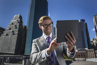 Young businessman using digital tablet touchscreen in front of office, New York, USA - ISF14035