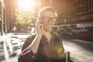 Happy young businessman strolling city street talking on smartphone, New York, USA - ISF14050