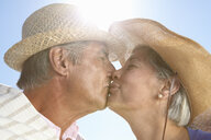 Couple wearing straw hats kissing - CUF33213