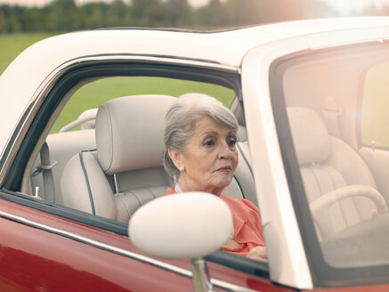 Senior woman driving red convertible - CUF33231