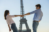 Young couple in front of  Eiffel Tower, Paris, France - CUF33240