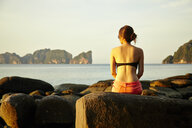 Young woman sitting on coastal rock, Phi Phi Islands, Thailand - CUF33345