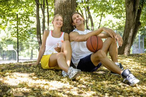 Basketball couple taking a break in park - CUF33351