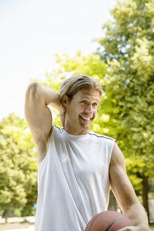 Male basketball player taking a break in park - CUF33360