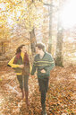 Couple running in forest holding hands - CUF33462