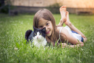 Portrait of little girl with cat lying on a meadow - LVF07124