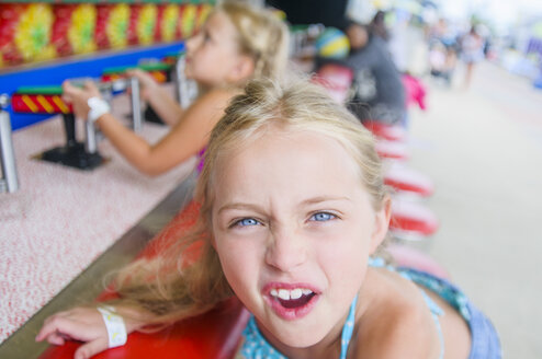 Portrait of girl pulling faces at fairground stall - ISF14122