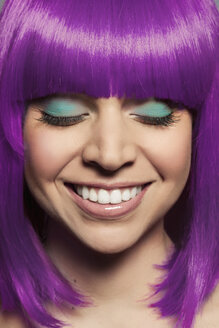 Mid adult woman wearing purple wig with eyes closed - ISF14131