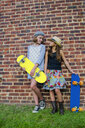 Two girl skateboarders looking at each other in front of brick wall - ISF14137