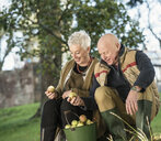 Senior couple admiring apples from bucket - CUF33560