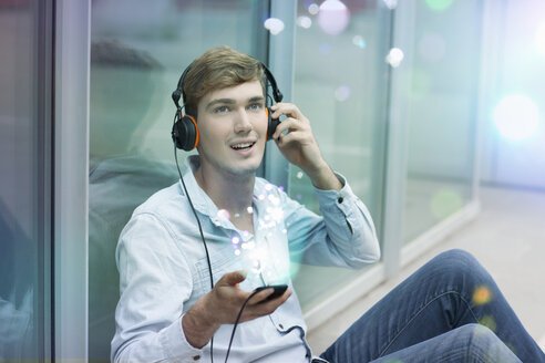 Young man with headphones and smartphone with lights coming out of it - CUF33611