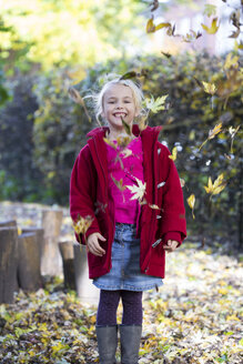 Portrait of laughing little girl throwing leaves in the air in autumn - JFEF00882